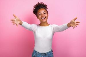 Portrait en studio d'une femme les bras écartés posent sur fond rose en regardant la caméra, concept d'amitié - image photo