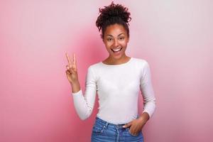jolie jeune femme montrant le geste de la victoire et regarde joyeusement photo
