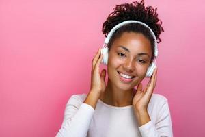 Portrait d'une jolie fille dans les écouteurs écoutant de la musique sur fond rose - image photo