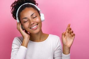 portrait d'une charmante fille aux yeux fermés dans les écouteurs écoutant de la musique sur fond rose photo