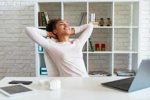 une femme heureuse fait une pause au bureau, les bras croisés par la tête et allongée sur la chaise en levant les yeux photo