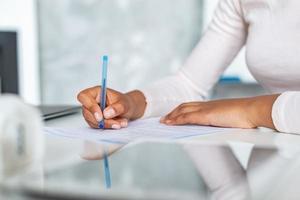 gros plan des mains des femmes pendant l'écriture avec un stylo sur un papier, femme d'affaires signant un document photo
