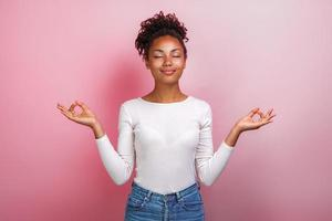 jolie fille debout les bras écartés dans le geste de la méditation avec les yeux fermés.- image photo