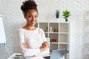 charmante femme au bureau, les bras croisés et souriante en regardant la caméra s'est penchée sur la table photo