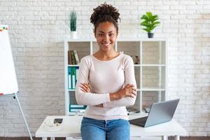 une femme heureuse se repose au bureau, les bras croisés et souriante en regardant la caméra se penche sur la table photo