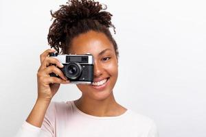 Close up portrait of a happy traveler girl with photo camera in her hand and looking in it - image