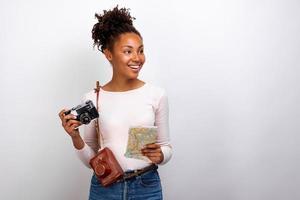 Portrait en studio d'une heureuse voyageuse mulâtre avec un appareil photo et une carte dans ses mains et regardant de côté- image