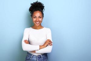 Happy african american woman bras croisés en se tenant debout sur fond bleu studio- image photo
