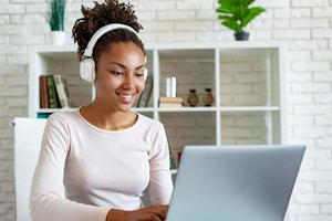portrait d'une femme mulâtre heureuse indépendante travaillant sur un ordinateur portable dans des écouteurs et écoutant de la musique photo