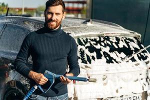 lavage de voitures. taille vue portrait de l'homme de race blanche tenant un équipement spécial et souriant à la caméra. voiture de nettoyage à l'aide du concept d'eau à haute pression. mise au point sélective photo
