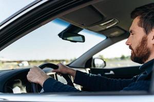 vue depuis la rue du bel homme d'affaires conduisant une voiture avant d'acheter. homme élégant et séduisant en affaires ferme la voiture de conduite. concept de transport photo