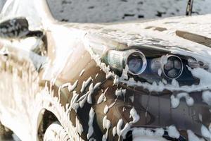 vue rapprochée de l'auto noire lavée par haute pression d'eau et de savon au lave-auto. concept de service de nettoyage. station de lavage automatique en libre service photo