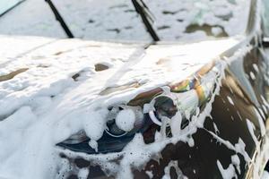 lavage de voiture en plein air avec du savon mousse. auto noire lavée par haute pression d'eau et de savon au lave-auto. concept de service de nettoyage. station de lavage automatique en libre service photo