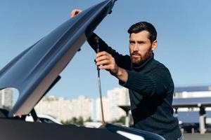 jeune homme regardant sous le capot de la voiture de dépannage. panne de voiture. jeune homme concentré essaie de réparer le moteur, regardant à l'intérieur tout en se tenant à l'extérieur photo