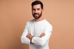 portrait de beau jeune homme barbu heureux debout avec les bras croisés et regardant la caméra avec un sourire à pleines dents. tourné en studio intérieur isolé sur fond beige photo