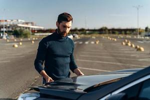 homme barbu contrarié vérifiant le moteur de sa voiture après une panne sur la route. un homme sérieux se tient devant le capot. concept de transport photo