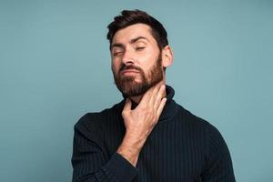 homme malade malheureux touchant le cou ressentant de la douleur en avalant, résultat d'un étouffement, d'une inflammation de la gorge, d'un mal de gorge. tourné en studio intérieur isolé sur fond bleu photo