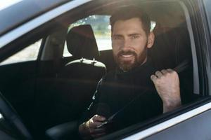 heureux homme caucasien assis et regardant la fenêtre tout en ayant une longue route en voiture. personnes occupées et concept de transport photo