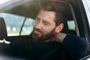 homme d'affaires fatigué en voiture ressentant une forte douleur au cou et une inflammation des nerfs, après une longue route. concept de problèmes de transport et de santé photo