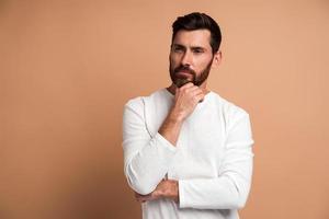portrait d'un beau jeune homme barbu pensif debout, touchant son visage, regardant de côté et pensant à quelque chose. tourné en studio intérieur, isolé sur fond beige photo