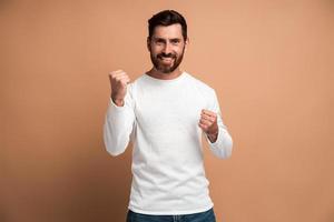 portrait d'un homme brune extatique avec une barbe montrant oui je l'ai fait un geste et un espace de copie réjouissant pour l'annonce. tourné en studio intérieur isolé sur fond beige photo