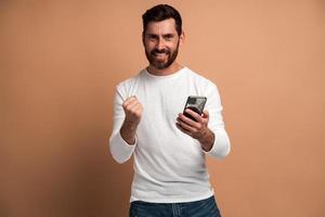heureux homme satisfait avec barbe tenant un smartphone et souriant faisant un geste oui, célébrant la loterie en ligne ou la victoire gratuite. tourné en studio intérieur isolé sur fond beige photo