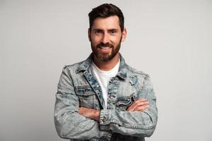 jeune homme barbu adulte portant une veste décontractée posant avec une expression faciale confiante et les bras croisés, regardant souriant à la caméra. Studio intérieur tourné isolé sur fond blanc photo
