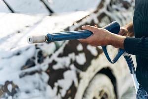 vue recadrée du jeune homme caucasien tenant un pistolet à haute pression tout en se préparant à pulvériser sur sa voiture pendant le nettoyage. stock photo