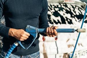 vue rapprochée du beau jeune homme tenant un pistolet à haute pression tout en se préparant à pulvériser sur sa voiture pendant le nettoyage. stock photo