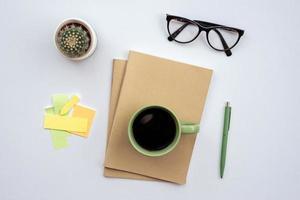 bureau avec verres, tasse de café debout sur un cahier - vue de dessus photo