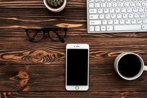 bureau vue de dessus avec une tasse de café et un smartphone et des lunettes photo