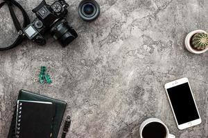vue de dessus un fond de plâtre avec un appareil photo, un smartphone et de la papeterie photo