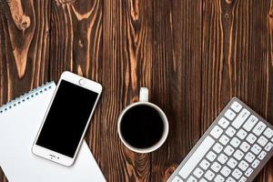 bureau en bois vue de dessus avec une tasse de café et un smartphone - copyspace photo