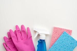 gants en latex, spray et liyng spongieux de cuisine sur fond blanc, espace de copie photo