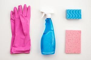 latex, gants roses, brosse de nettoyage, spray, gant de toilette, chiffon sur fond blanc. photo