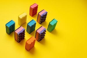 armée de débarbouillettes colorées disposées sur fond jaune. photo