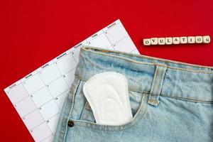 suivi du cycle menstruel et de l'ovulation. sur un fond rouge les tampons des femmes dans la poche de jeans. photo