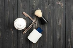 vue de dessus, sur un fond en bois foncé outils de rasage, baume après-rasage, rasoir photo