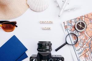 fond blanc avec des choses pour passeport de voyage, lunettes de soleil, loupe, capuche, boussole, coquillage photo