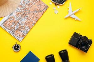 préparation pour voyager, argent, passeport, avion, chapeau, jumelles, appareil photo, carte, sur fond blanc. photo