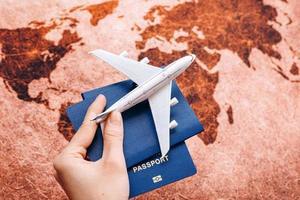 main tenant un passeport sur fond de carte du monde avec modèle d'avion, concept de voyage, mise au point sélective photo