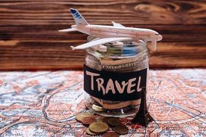 collecter de l'argent pour voyager, économiser de l'argent dans un bocal en verre avec carte du monde photo