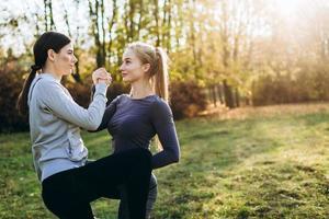 deux copines effectuent des exercices en face à face dans la nature. photo