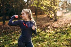 fille avec des haltères regarde les biceps, entraînement dans la nature photo