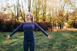 belle fille souriante au gymnase du matin dans le parc, regardant loin avec les bras tendus. photo