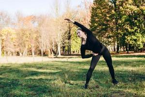 fille en vêtements de sport noirs effectue une inclinaison d'exercice à gauche à l'extérieur, jour d'automne. photo