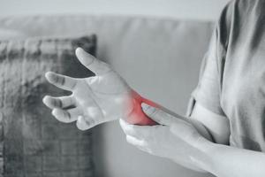 gros plan d'une femme assise sur un canapé tient son poignet, blessure à la main avec surbrillance rouge, sensation de douleur. soins de santé et concept médical. photo