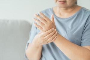 gros plan d'une femme assise sur un canapé tient son poignet. blessure à la main, sensation de douleur. soins de santé et concept médical. photo