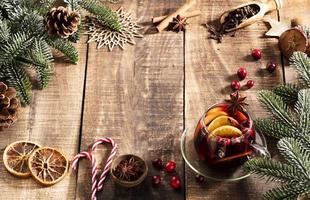 vin chaud de noël aux épices sur une table rustique en bois. photo