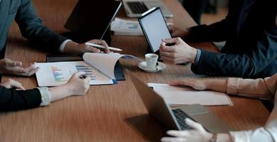 collègues lors d'une réunion dans la salle de réunion, assis à table ensemble, partageant des idées, discutant de la stratégie du projet. photo